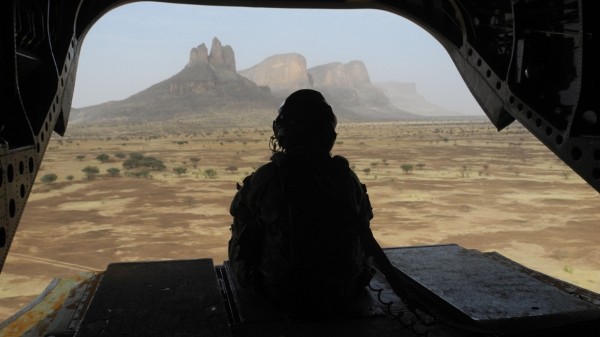 A soldier sits in the back of a helicopter