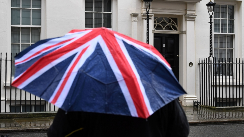 A person holds a Union flag outside Number 11 Downing Street