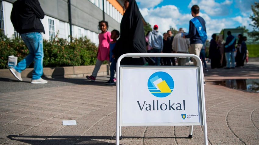 People walk past a voting location sign in Sweden